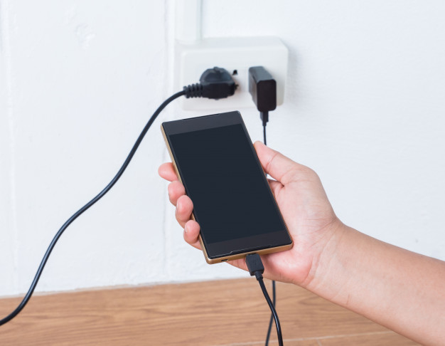 hand-holding-mobile-phone-charging-plugged_50401-64